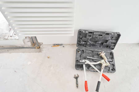 Tools for Work As A Plumber. Connection heating pipes to white Radiator in a new apartment under construction. water heating radiator on the white wall indoors