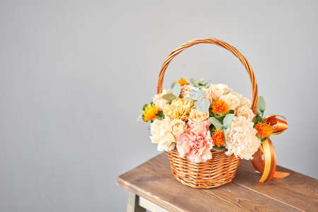 Small flower shop and Flowers delivery. Flower arrangement in Wicker basket. Beautiful bouquet of mixed flowers in woman hand. Handsome fresh bouquet Standard-Bild