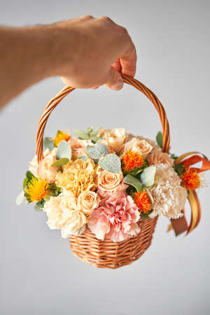 Small flower shop and Flowers delivery. Flower arrangement in Wicker basket. Beautiful bouquet of mixed flowers in woman hand. Handsome fresh bouquet 版權商用圖片
