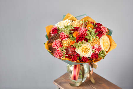 Autumn, Red tones Beautiful bouquet of mixed flowers in womans hands. the work of the florist at a flower shop. Handsome fresh bouquet. Flowers delivery Standard-Bild
