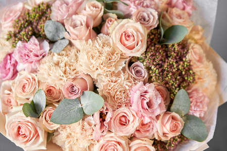 Beautiful spring bouquet on wooden table.. Arrangement with various flowers. The concept of a flower shop. A set of photos for a site or catalogue. Work florist. Standard-Bild