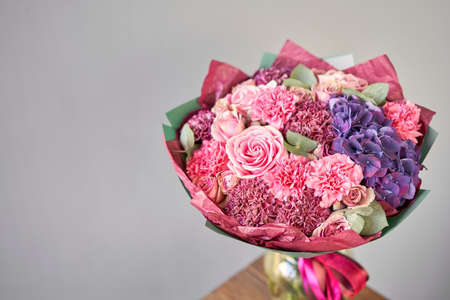 purple and pink bouquet of beautiful flowers on wooden table. Floristry concept. Spring colors. the work of the florist at a flower shop.