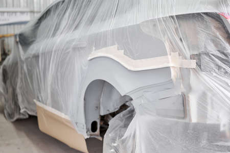 Garage painting car service. section of the car is covered with primer. vehicle is covered with protective paper. Repairing car body work after the accident by working sanding primer before painting.