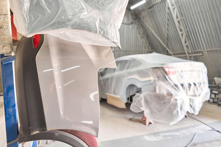 Focus on spare parts. Garage painting car service. section of the car is covered with primer. vehicle is covered with protective paper.