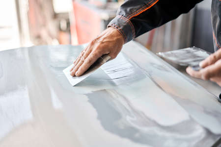 Repairing car body, Application putty close up. The mechanic repair the car. Work after the accident by working sanding primer before painting. Standard-Bild