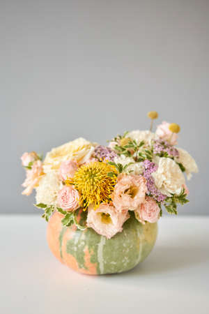 Flowers arrangement in pumpkin on the white table. Fresh cut flowers for decoration home. European floral shop. Delivery fresh cut flower.