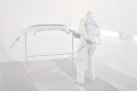 All in a haze of paint. Worker painting parts of the car in special painting chamber, wearing costume and protective gear. Car service station.