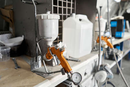 Image of Spray gun. Worker painting parts of the car in special painting chamber, wearing costume and protective gear. Car service station. Standard-Bild