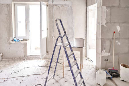 Aluminium ladder in a room under construction works. Repair process in an empty bright room. Empty interior for design, gray concrete wall.