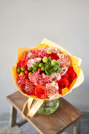 Red and green flowers. Autumn bouquet of mixed flowers in glass vase on wooden table. The work of the florist at a flower shop. Fresh cut flower.