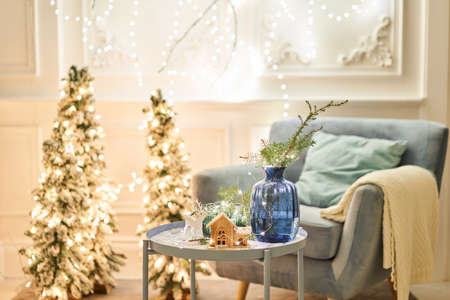 Classic apartments with decorated christmas tree and presents. Christmas evening in the light of candles and garlands. Living with fireplace and stucco.