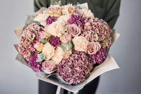 Beautiful bouquet of mixed flowers in womans hands. the work of the florist at a flower shop. Delivery fresh cut flower. European floral shop.