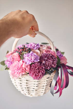 Flower arrangement in Wicker basket. Beautiful bouquet of mixed flowers in woman hand. Handsome fresh bouquet. Small flower shop and Flowers delivery.