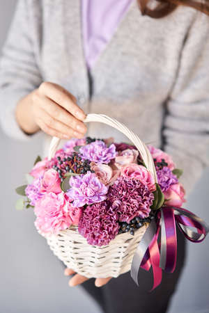 Small flower shop and Flowers delivery. Flower arrangement in Wicker basket. Beautiful bouquet of mixed flowers in woman hand. Handsome fresh bouquet Imagens