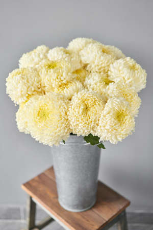 Mono bouquet of chrysanthemum in metal vase. European floral shop. the work of the florist at a flower shop. Delivery fresh cut flower.