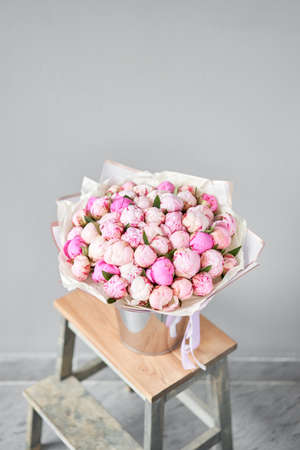 Pink peonies in a metal vase. Beautiful peony flower for catalog or online store. Floral shop concept . Beautiful fresh cut bouquet. Flowers delivery