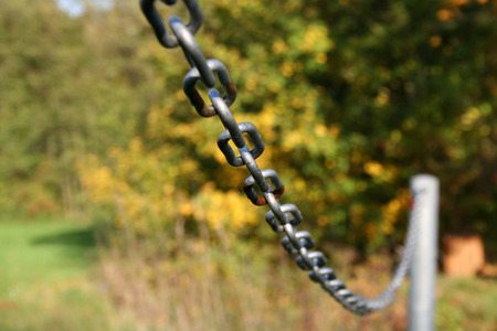 defines: Sturdy chain of iron on a lawn. Robust iron chain Defines green of a lawn. Stock Photo