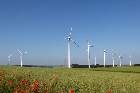 Windmill generator in wide yard. Yard of windmill power generatorunder blue sky, shown as energy industry concept.