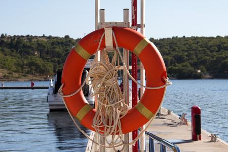 safety buoy: cruise, boating, preserver, nautical, safety, white, sauce, red, help, lifebelt, lifebuoy, buoy, marine, life, safe, boat, rope, circle, sea, ring, orange, insurance, background, water, rescue, Lifeguard, security, belt, ocean