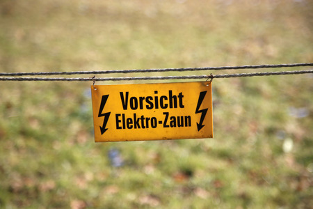 sheep warning: Electric fence  text: Caution, electric fence! Stock Photo