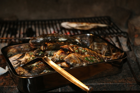 Fish grill on the grill and grilled. Fresh raw fish on the grill. Cooked in traditional style. Cooking salted fish on a barbecue stove. Standard-Bild - 111689828