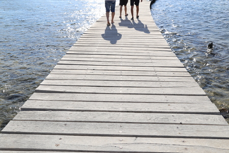 People walk along the wooden bridge Standard-Bild - 110625782