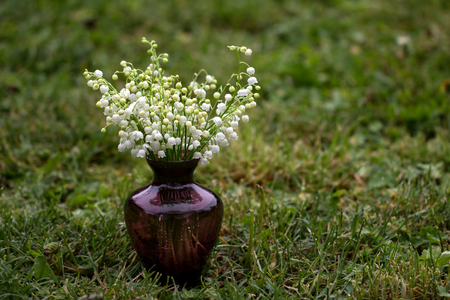 Vase with lilies of the valley.