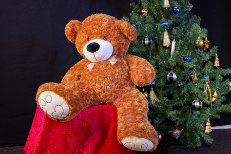 Teddy bear on the background of a Christmas tree