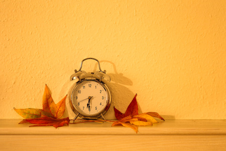 Autumn still life  alarm clock and autumn leaves