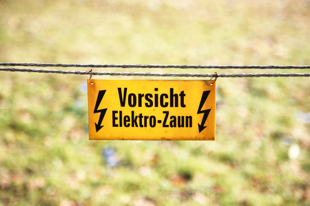 Warning sign. Electric fence / text: Caution, electric fence! Standard-Bild - 115687040
