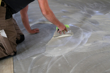lavoratore che installa un nuovo pavimento in piastrelle di vinile.