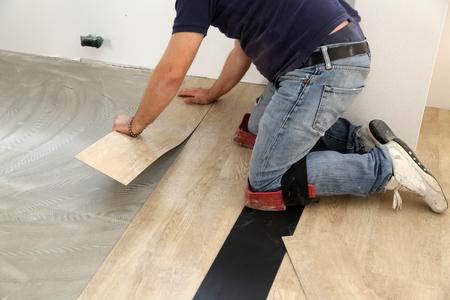 worker installing new vinyl tile floor.