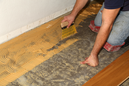 Parquet flooring. Worker laying parquet flooring