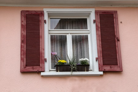 Windows with shutters. Flowers on the windowsill Standard-Bild - 114622604