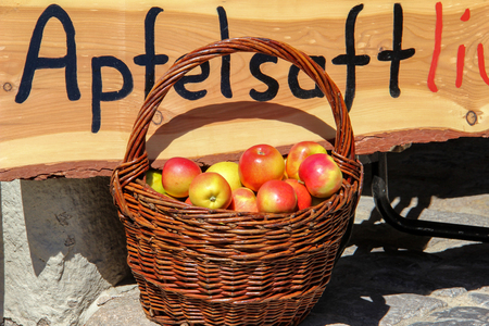 Basket with ripe apples. The inscription in German: Apple juice. Standard-Bild - 114623189