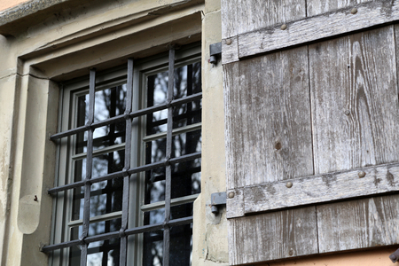 A window with bars and shuttered in the old castle Standard-Bild - 116009653