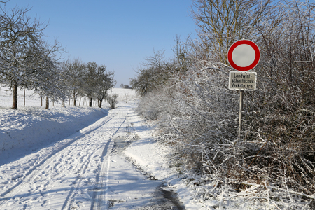 Winter field road on a clear sunny day. The inscription under the sign in German: Agricultural vehicles only Standard-Bild - 116009692