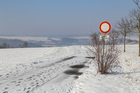 Winter field road on a clear sunny day. The inscription under the sign in German: Agricultural vehicles only Standard-Bild - 116009693