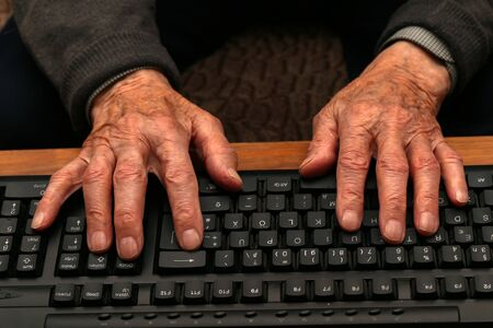Hands of the old man on the keyboard