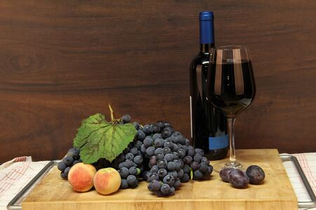 Glass of red wine, grapes and peaches