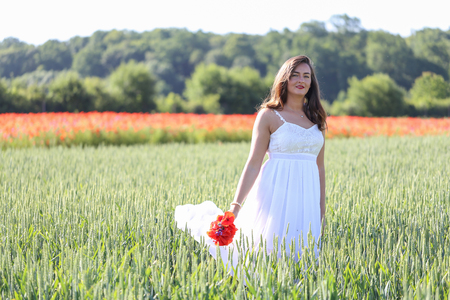 Portrait of a girl with poppies in wheat field.