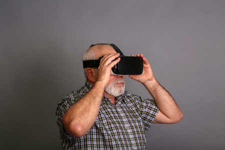 Man wearing virtual reality goggles. Studio shot, gray background
