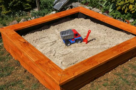 Neu gebauter Sandkasten für kleine Kinder im Garten.