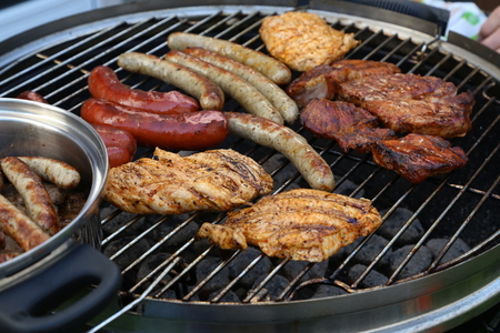 Meat and sausages are fried on the grill. Stockfoto