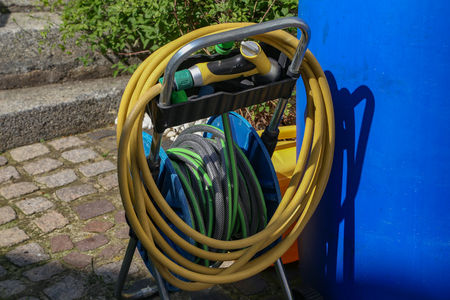 Bright watering garden hose near the house