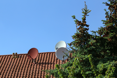 Satellite antennas on the roof of the house.