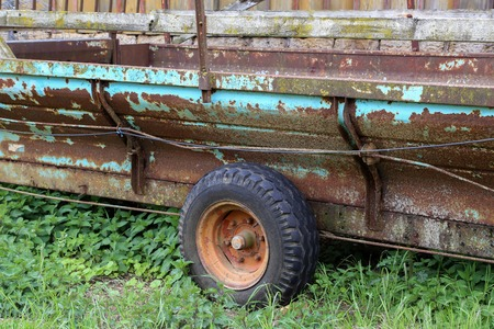 Old Tractor cart stands at a wooden barn. Imagens
