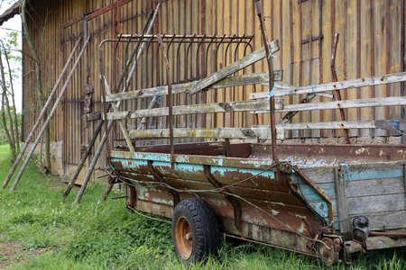 Old Tractor cart stands at a wooden barn. Stockfoto