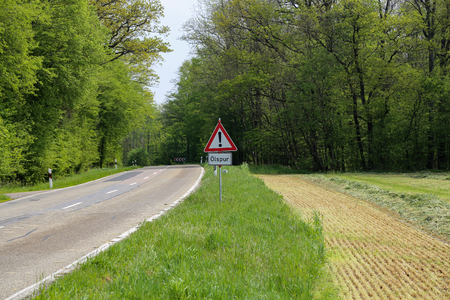 Warning road sign on the edge of the road. German text: oil track