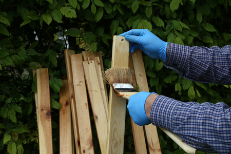 The worker paints wooden slats with protective varnish.